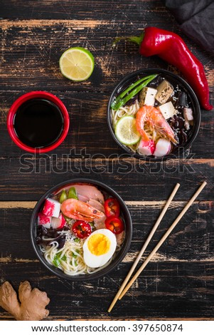 Table served with asian noodle soup in a black bowls with chopsticks, soy sauce, sliced lime and ginger on a dark textured wooden background. Asian style dinner. Top view - stock photo