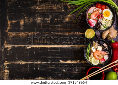 Table served with asian noodle soups in a black bowls with chopsticks, soy sauce, sliced lime, ginger on a dark textured wooden background. Space for text. Asian style dinner. Ingredients for cooking - stock photo