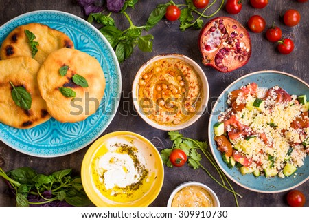 Table served with middle eastern traditional vegetarian dishes. Hummus, tahini, pitta, couscous salad and buttermilk dip with olive oil. Dinner party - stock photo