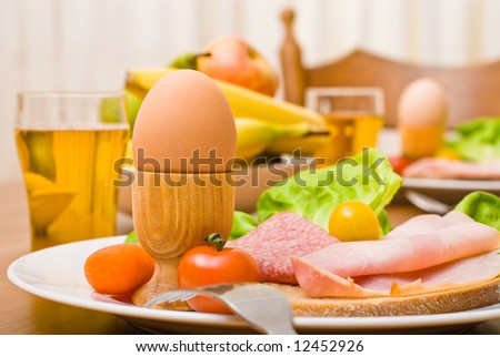 Table served with snacks. Fruits, vegetables, bread, egg, ham etc. Focus on the front egg, shallow depth of field.