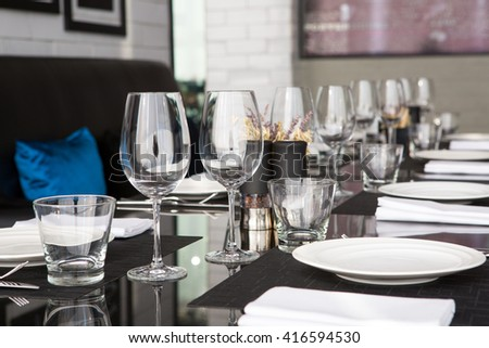 Table service in the restaurant. Transparent clean glasses and wine glasses. - stock photo