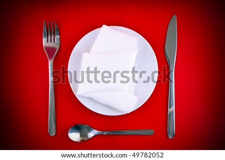 Table serving-knife, fork and silk napkin on red  background.Spotlight source on top and in center.