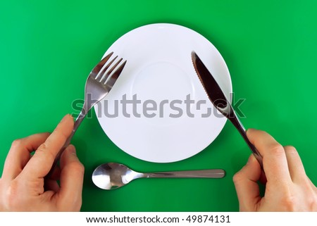 Table serving- knife, fork  in a hands  on green   background.