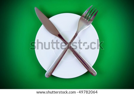 Table serving-knife, fork   on green  background.Spotlight source on top and in center.