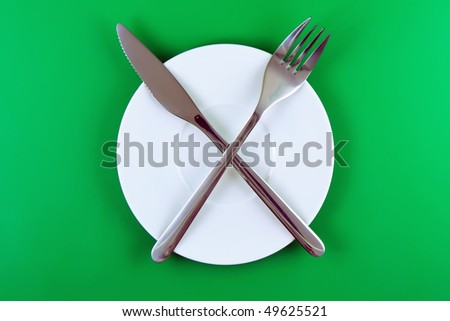 Table serving- knife, fork on green   backgroung.
