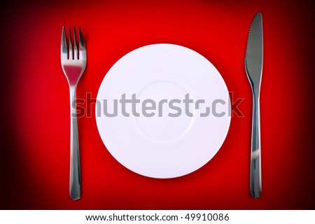 Table serving-knife, fork  on red background.Spotlight source on top and in center. - stock photo
