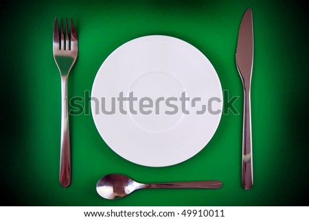 Table serving-knife, fork, spoon   on green background.Spotlight source on top and in center.