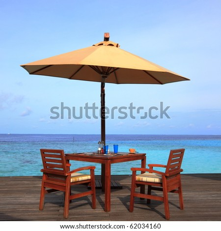 table set and umbrella on the deck - stock photo