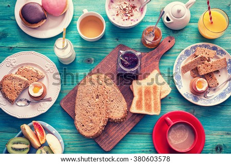 Table set for a typical  breakfast with poached eggs,butter,preserves like strawberry jam and apricot jam,orange juice,coffee and fresh fruits - stock photo