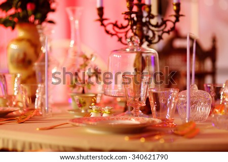Table set for an event party or wedding reception in red light - stock photo