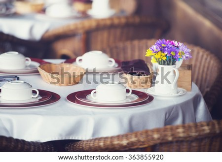 Table set for dinner in a restaurant or bistro with dinnerware and linen and a small vase of colorful flowers