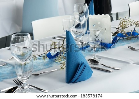 Table set for dinner party in white and blue - stock photo