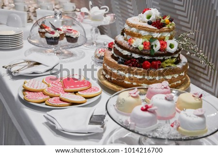 Table set for wedding arrangement with cake, cupkakes and cookies