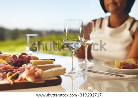 Table set in the winery with two glasses of wine, cheese and grapes. Woman sitting in back at winery restaurant table.