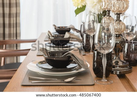 table set on wooden dinning table with vase of plant
