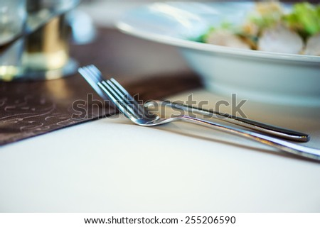 table set service with silverware and glass stemware at restaurant - stock photo