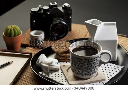Table set with coffee, notebook and camera