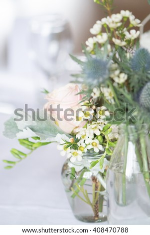 Table set with vintage flowers - simple relaxed style  flowers in vintage glass jars for wedding reception or party