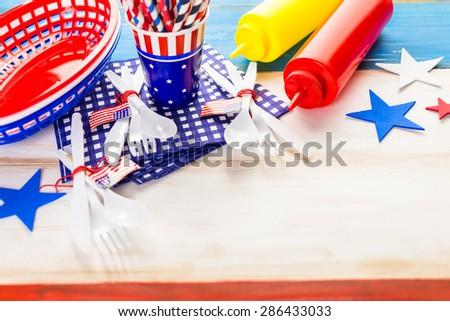 Table set with white, blue and red decorations for July 4th barbecue.