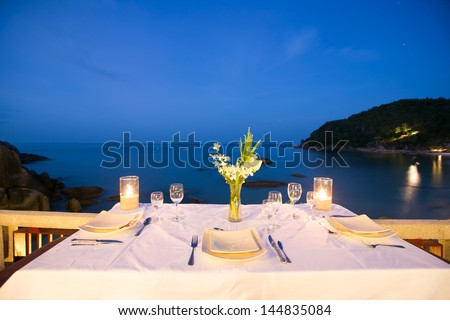 Table setting at beach restaurant in twilight time. - stock photo