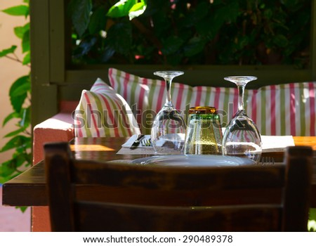 Table setting at greek cafe terrace - stock photo