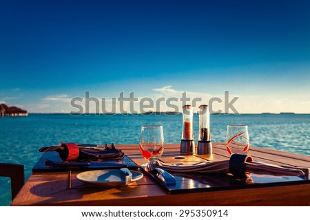 Table setting at tropical beach restaurant during summer sunset - stock photo