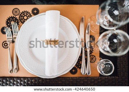 Table setting at wedding. Steampunk style. Glasses. plates, cutlery on craft paper. Shot from above. - stock photo