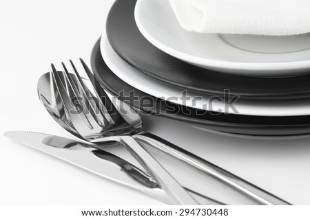 Table setting: black and white plates and cutlery set on white background.  - stock photo