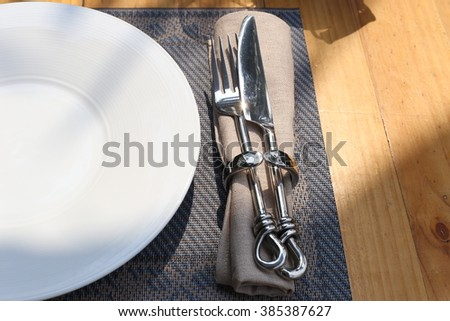 Table setting. Close up of fork and knife hold in napkin ring with napkin on a plate mat. Part of porcelain plate on the left. Shot in morning sunlight, shadow on the scene.
