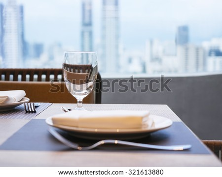 Table setting dinner Restaurant interior with City Skyline view - stock photo