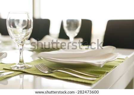 Table setting for a business lunch. Plate with napkin, silverware and wineglass. Close up. - stock photo