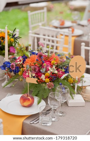 Table setting for a outdoor wedding with rich bunch of flowers - stock photo