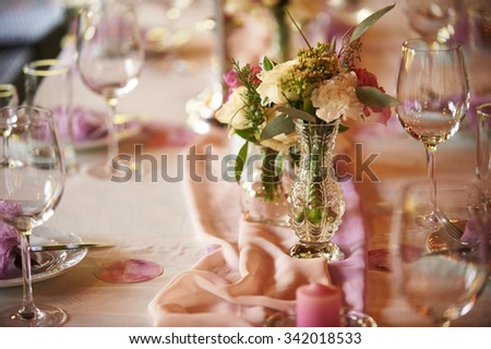 Table setting for a wedding in peach tones. Plates and wine glasses are on the peach tablecloth with purple decorative pieces of matter. The table is decorated with bouquets of flowers and candles