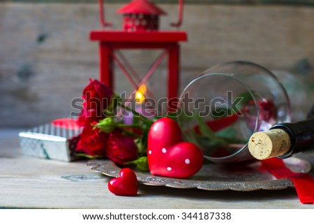 Table setting for St. Valentines day with glasses of red wine, present box and red roses  in rustic style - stock photo