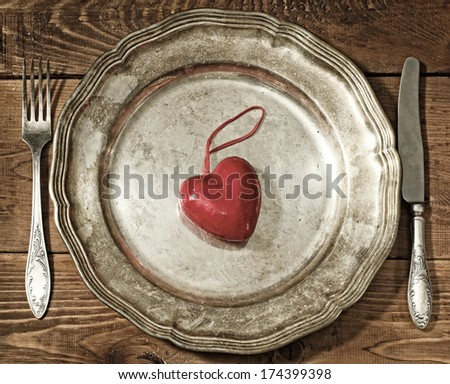 table setting for Valentine's Day. plate, fork, knife and red hear - stock photo