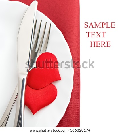table setting for Valentine's Day. plate, fork, knife and red hearts - stock photo