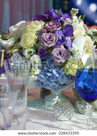 Table setting for wedding or event? bouquet of roses, orchids and freesia - stock photo