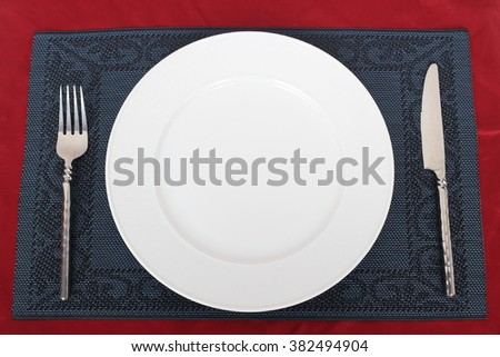 Table setting, fork, knife and plate on a dark plate mat. All are set on a red table cloth.