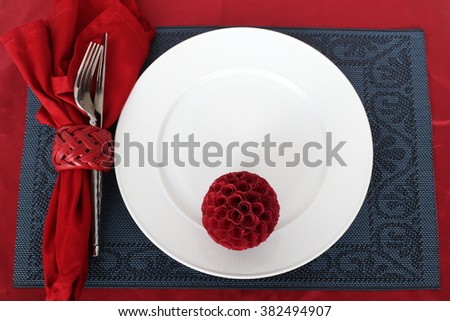 Table setting, fork, knife and plate on a dark plate mat with red napkin roll up in a red napkin ring. A red ball as decoration on the dish. All are set on a red table cloth.