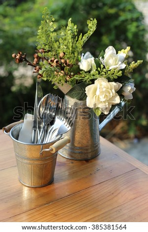 Table setting. Forks, knifes and spoons in vintage style zinc cutlery holder and artificial flowers in zinc watering can, Set on wooden table. - stock photo