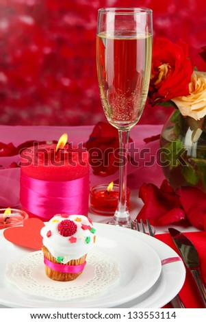 Table setting in honor of Valentine's Day on red background - stock photo