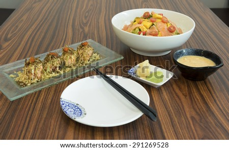 Table setting of a light meal of raw salmon salad and cooked salmon maki sushi topped with roe and serve with goma sauce, pickled ginger and wasabi. - stock photo