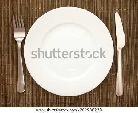 table setting of plate, fork and knife on dark background