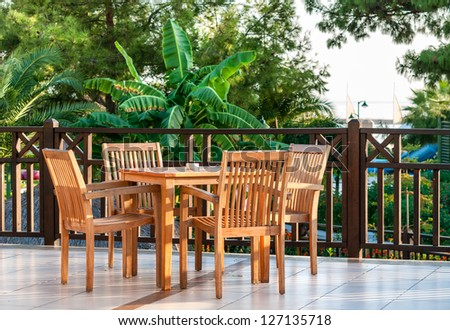 Table setting on a terraced lounge at a mediterranean resort hotel overlooking the sea - stock photo