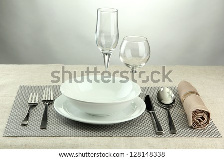 Table setting, on grey background - stock photo