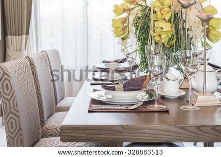 table setting on wooden dinning room with vase of flower, interior design