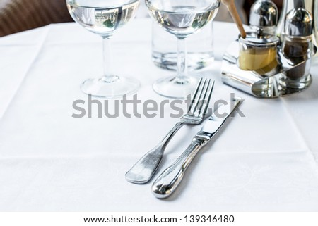 table setting - plate, knife and fork on table - stock photo