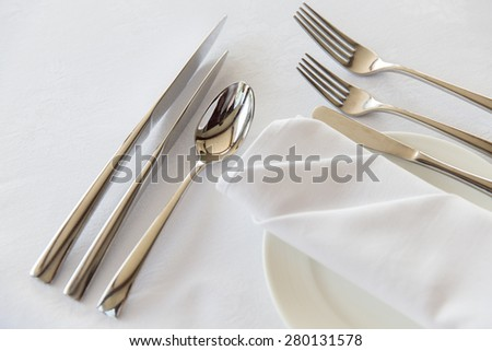 table setting, silverware and eating concept - close up of cutlery set wrapped with napkin and plate on restaurant table - stock photo