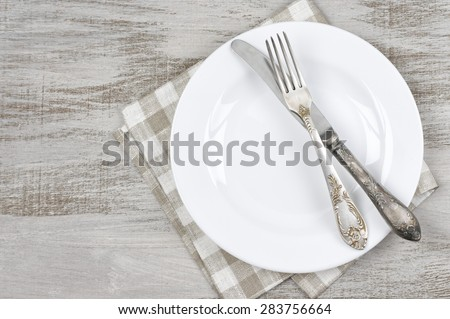 Table setting: white plate, vintage fork and knife with napkin on rustic wooden table. Top view point. - stock photo