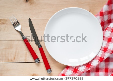 Table setting with a plate, cutlery and napkin in red and white colors. View from above with copy space